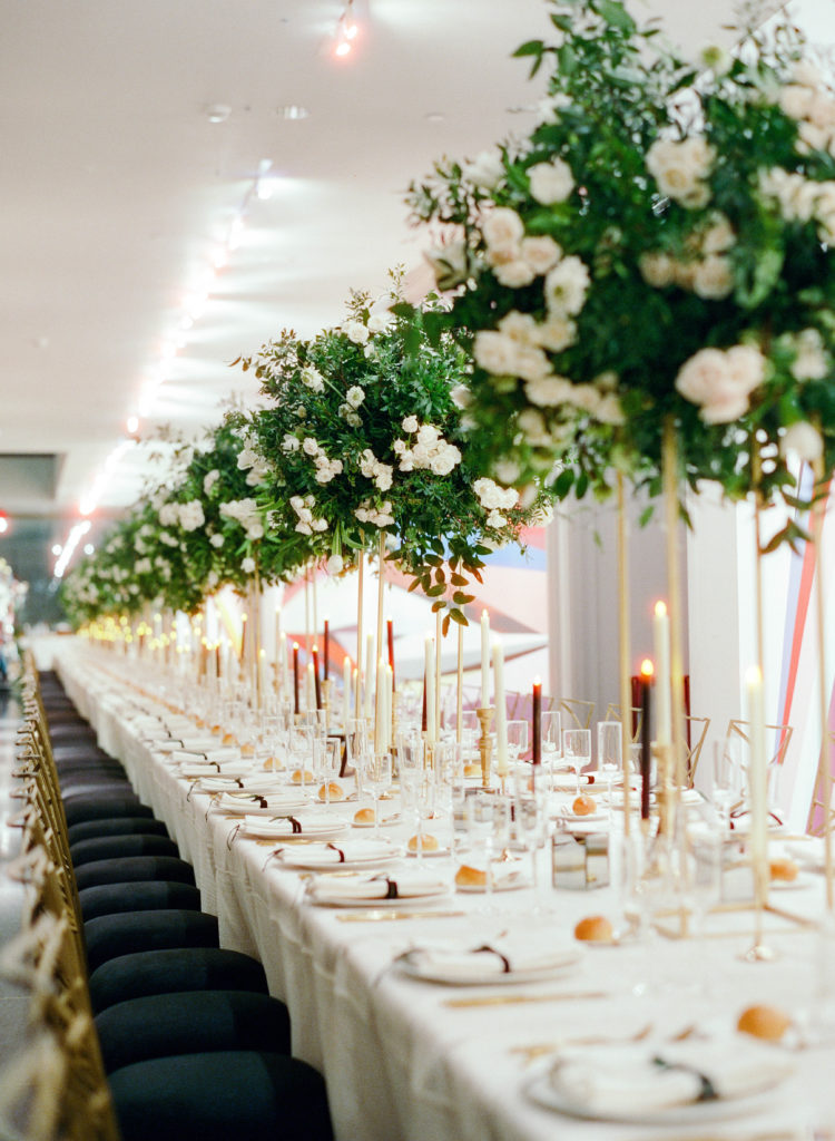 long row of tall white and green flower arrangements on a dinner table in an art museum