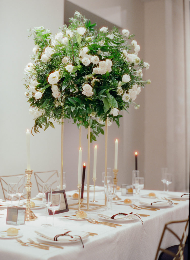one tall floral arrangement with white flowers and green leaves on a dinner table