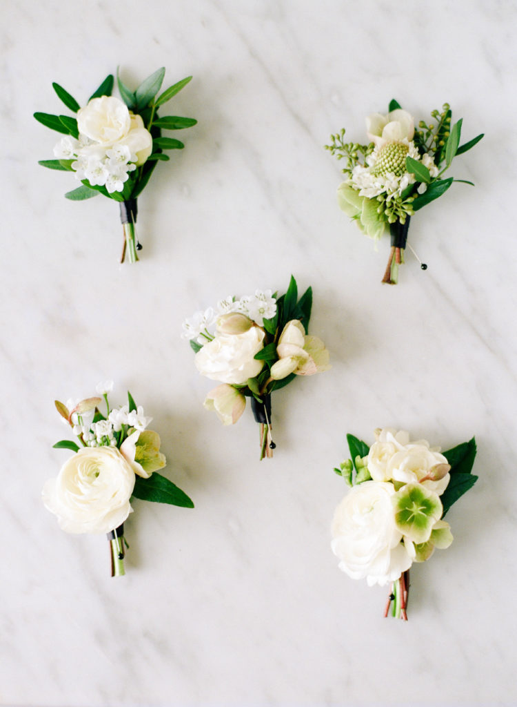 five white and green boutonnieres