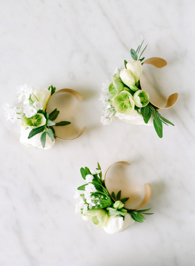three gold cuff bracelets with white and green flowers