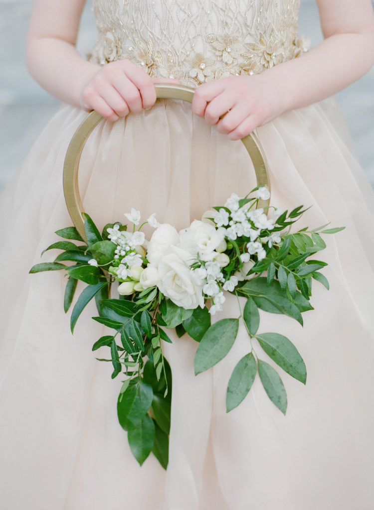 flower girl holding a gold hoop with white glowers and greenery, clsoeup